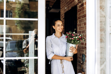 Beautiful brunette girl dressed in a striped dress holds a vase