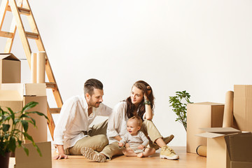 Couple moving to a new home. Happy married people with newborn child buy a new apartment to start life together. The family at repair and relocation planing to accommodation against boxes