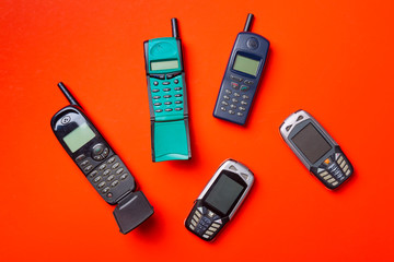 Old vintage mobile cell phones on red orange background