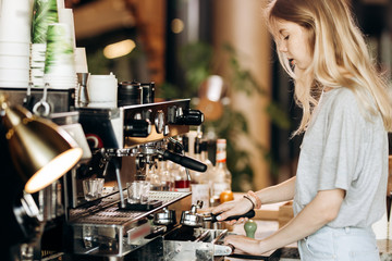 A young pretty thin blonde,dressed in casual outfit,is cooking coffee in a popular coffee shop.