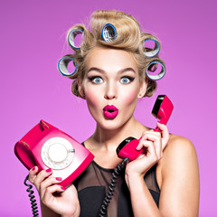 young woman with wonder face holds retro phone