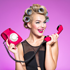 Cheerful angry caucasian woman yelling at retro telephone.