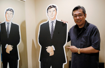Kenshi Hirokane, the comic book author of the Kosaku Shima and Like Shooting Stars in the Twilight series, poses with a cutout of Kosaku Shima character during an interview with Reuters at his studio in Tokyo