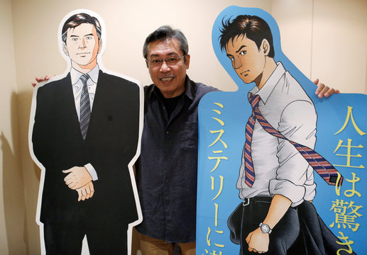 Kenshi Hirokane, the comic book author of the Kosaku Shima and Like Shooting Stars in the Twilight series, poses with cutouts of Kosaku Shima characters during an interview with Reuters at his studio in Tokyo