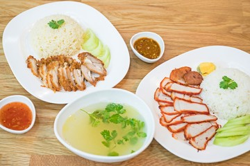 Rice with roasted red pork and Crispy roasted belly pork chinise style and rice. top view thai food on wooden table.