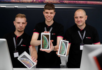 Employees pose for a picture during the launch of the new iPhone XS and XS Max sales at a shop in Moscow