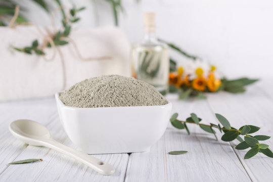 Preparing cosmetic mud mask with various skincare products. Dry clay powder in bowl. Natural cosmetics for home or salon spa treatment. On white background.