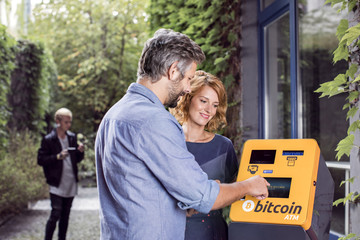 Couple in front of Bitcoin ATM