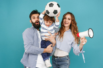 The happy father, mother and son playing together with soccer ball on blue studio background