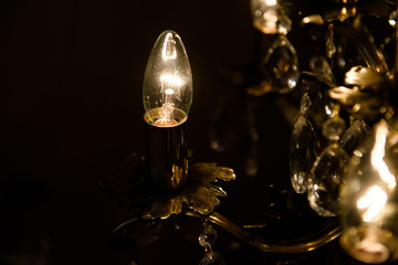 Light of the candle lit in a dark room. Vintage electric lighting in the room.