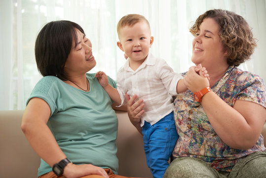 Cheerful lesbian couple playing with son at home