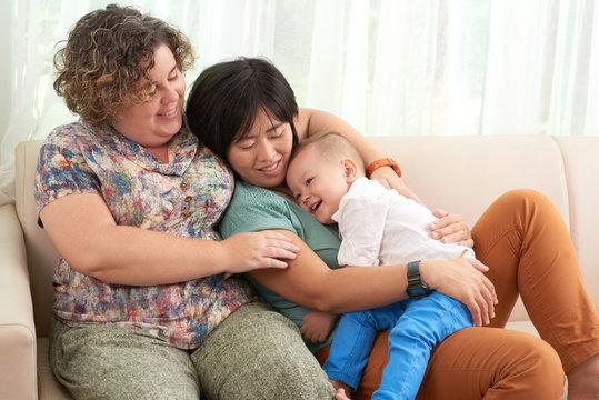 Joyful mixed-race lesbian couple resting on sofa with their cute little son