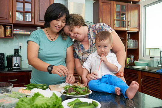 Homosexual couple in love with little child cooking dishes for lunch