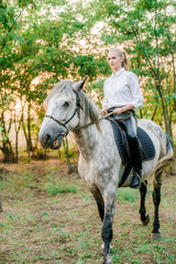 Beautiful young girl  with light hair in uniform competition smiling and astride a horse in sunset in autumn