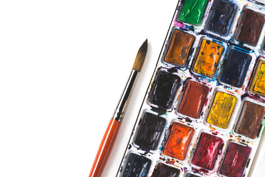 top view of paintbrush and colorful watercolor paints on white background