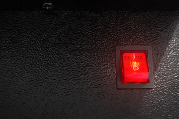 Red power switch on dark background. Electric control button.