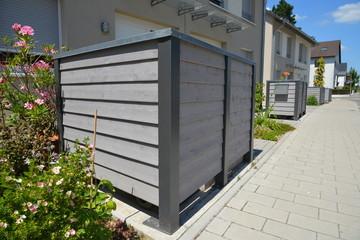 Stationäre Einhausung von Abfall-Sammelbehältern als Sichtschutz vor Wohnhäusern im Neubaugebiet