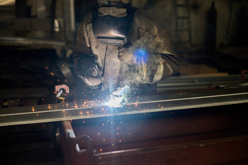 Worker in a special suit and mask performs welding work at an industrial factory