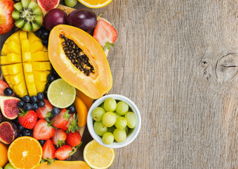 Overhead view of colorful fruits, strawberries blueberries, mango orange, grapefruit, banana papaya apple, grapes, kiwis on the grey wood background, copy space for text, selective focus