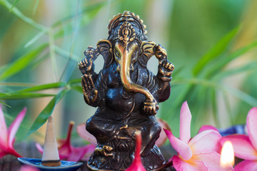 Statue of Ganesha Indian Hinduism God of wisdom and prosperity and heap of plumeria frangipani flowers