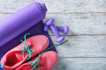 Yoga mat with sport shoes and dumbbells on light wooden background
