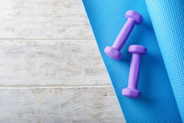 Yoga mat with dumbbells on light wooden background