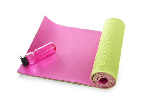 Yoga mat with bottle of water on white background