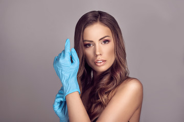 Attractive woman with stylish makeup putting on hands latex gloves