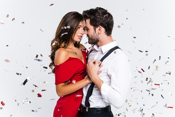 Heart to heart. Young beautiful couple dancing while standing against white background with confetti