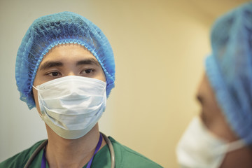 Young Asian surgical intern listening to advice of his coworker