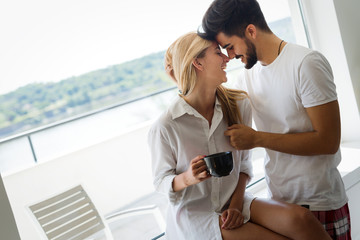 Beautiful young couple drink coffe, looking each other