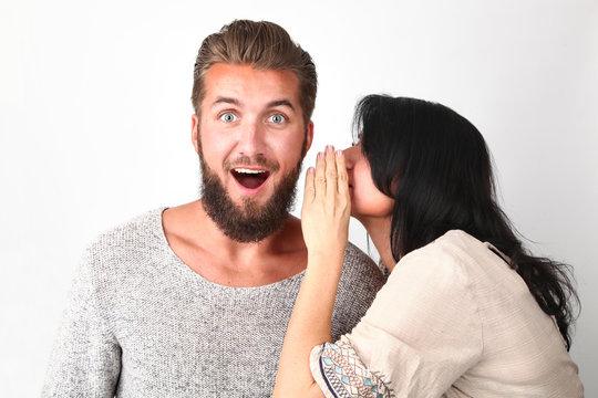Junge Frau flüstert ein Geheimnis in das Ohr ihres Freundes