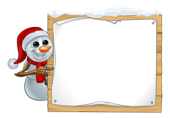 A snowman Christmas cartoon character wearing a Santa Claus hat and pointing at a sign