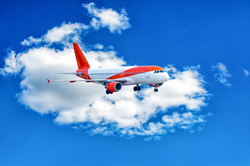 Red and white aeroplane in blue cloudy sky.