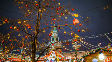 Photo of tree with golden and red balls on background of buildings with burning garland