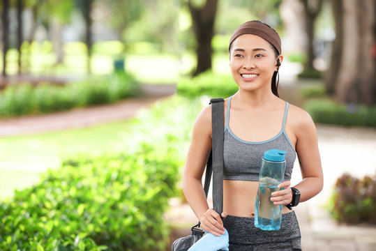 Happy slim Asian woman in sportswear holding bottle of water and carrying bag walking in park