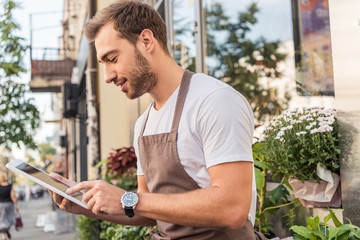 side view of handsome florist using tablet near flower shop