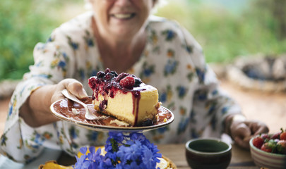 Grandmother holding a slice of cheesecake with mixed berries sauce