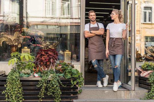 smiling coworkers standing in open door of flower shop