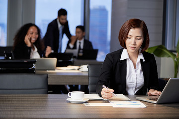 Young elegant Asian woman in office with colleagues sitting at table and working with paper documents