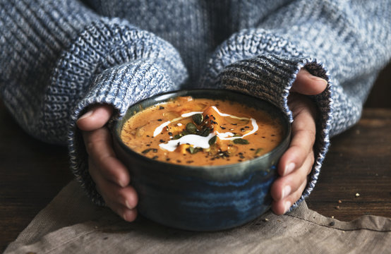 Female hands holding a bowl of pumpkin soup