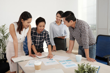 Young Asian business people discussing financial documents on office table