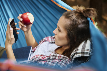 Woman relaxing on hammock and using mobile phone