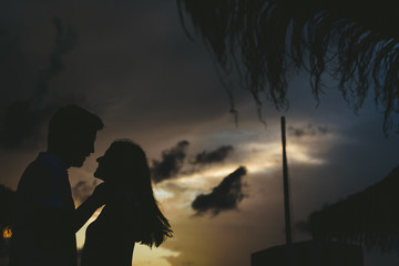 Silhouette of couple looking at each other in front of sunset in backlight.