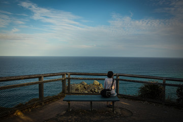 Woman on bench with seascape