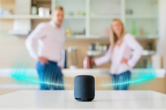 Couple talking and listening to smart speaker at home