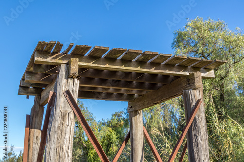 Old timber tank stand against blue sky