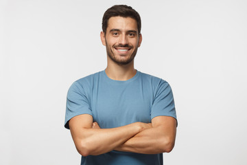 Indoor portrait of young european caucasian man isolated on gray background, standing in blue t-shirt with  crossed arms, smiling and  looking straight at camera Wall mural