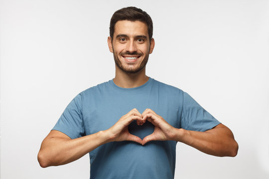 Young smiling handsome smiling male in blue t-shirt showing heart sign isolated on gray background