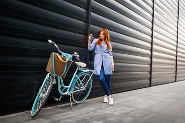 Woman standing near bike and making selfie